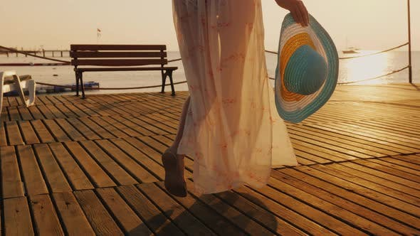 Thumbnail for A Woman Walks the Pier Towards the Rising Sun