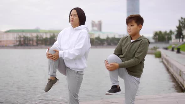 Thumbnail for Sportive Asian Mother and Son Working Out on Urban Riverside