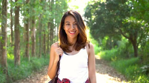 Young Asian woman traveler with backpack walking in forest.Adventure backpacker travel people.