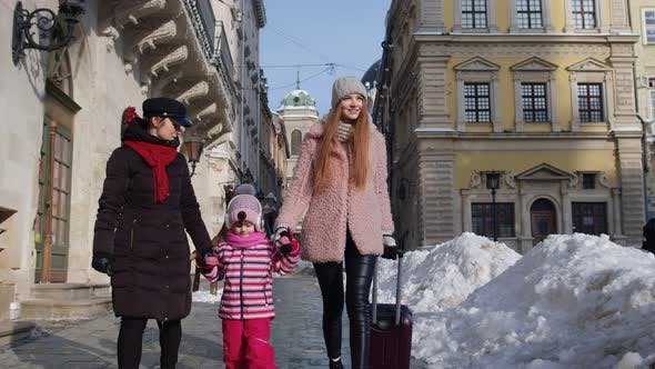 Two Young Smiling Women Tourists with Adoption Child Girl Walking with Suitcase on Old City Streets