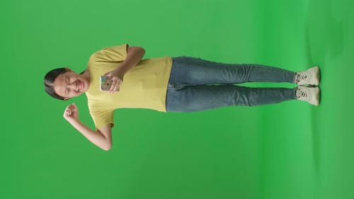 Full Body Of Asian Kid Girl Surprise And Celebrating During Use Mobile Phone On Green Screen