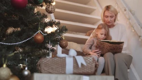 Mom and Daughter Reading Book on Christmas