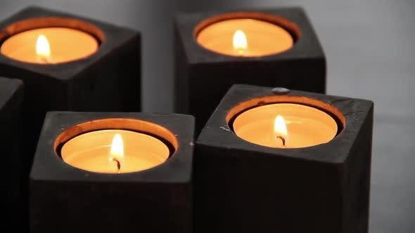 Thumbnail for A set of black stone block candle holders with lit tealight candles on a livingroom stone table.