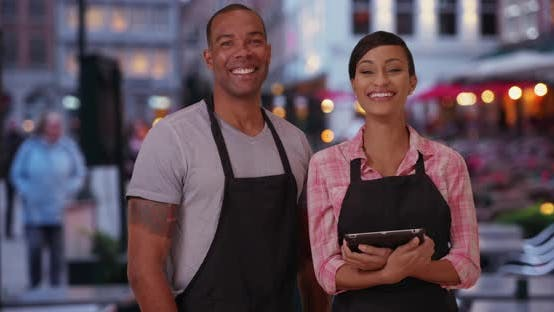 Thumbnail for Smiling African waiter and waitress posing confidently at outdoor restaurant