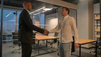 Two Entrepreneurs Shaking Hands Indoor in Modern Office