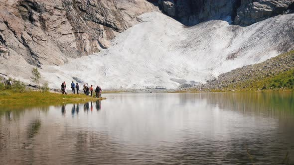 Thumbnail for A Group of Tourists Near a Small Lake and a Glacier in Norway. Scandinavian Nature and Tourism