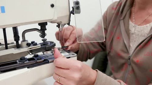 Woman Working on a Sewing Machine for Buttons