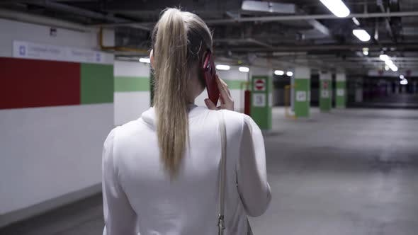 Walking Young Woman with Pony Tail White Shirt and Black Skirt in Garage