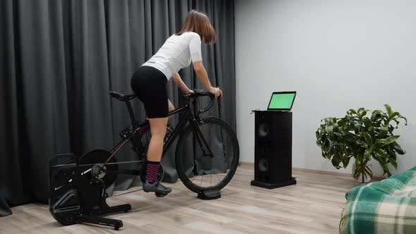 Thumbnail for Indoor Virtual Cycling, Fit cycling woman rides bicycle at home on stationary bike out of saddle
