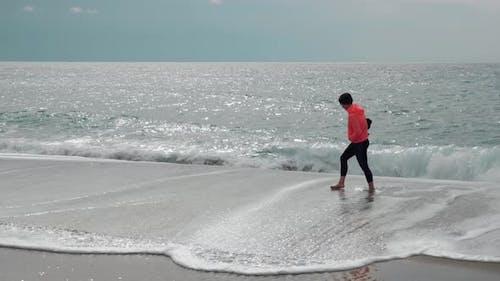 Female is walking on empty sandy beach