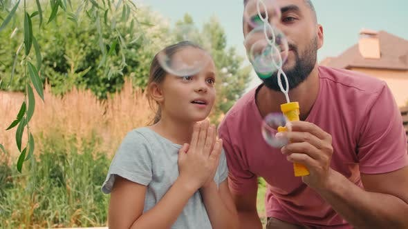 Dad And Little Girl Blowing Bubbles Outdoors