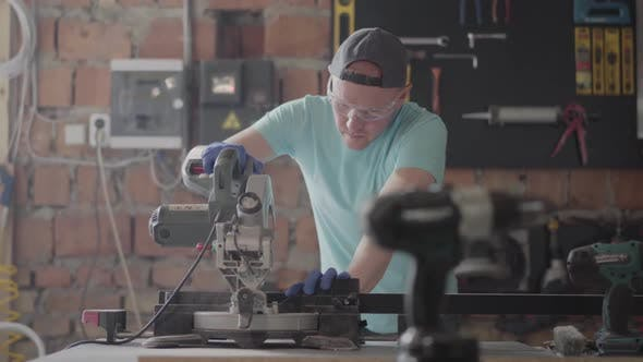 Cover Image for Portrait Craftsman in Protection Glasses Cutting a Wooden Board with a Small Circular Saw on the