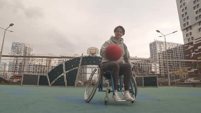 Woman in Wheelchair Dribbling on Court