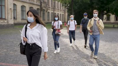 Multiracial Students in Face Masks Going to Class