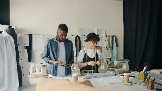 Creative Dressmakers Designing Clothing Using Tablet and Measure-tape in Studio
