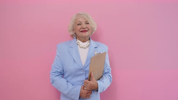 Portrait of a Stylish Elderly Woman in an Elegant Business Suit Holding a Tablet and Smiling at the