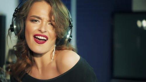Woman singing in a recording studio. Female vocals. Professional recording studio.
