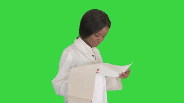 Thumbnail for Smiling African American Female Doctor Reading Cardiogram on a Green Screen, Chroma Key.