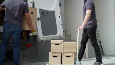Tracking video of delivery men loading parcels onto a delivery truck.