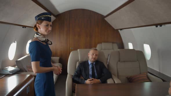 Private Jet Cabin with Businessman in Armchair. Luxury Service From Stewardess