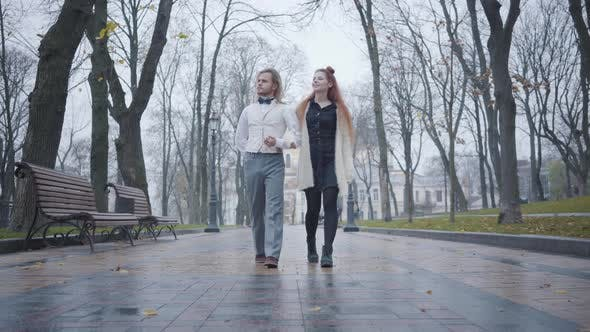 Thumbnail for Young Caucasian Man with Long Hair and Redhead Woman Walking Along the Alley in Autumn City Park