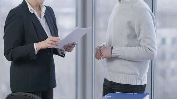 Unrecognizable Man and Woman Passing Documents and Shaking Hands in Office