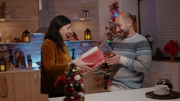 Man and Woman Giving Gift Boxes to Each Other for Christmas