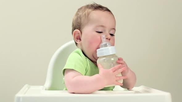 Baby boy sitting in highchair with bottle of milk
