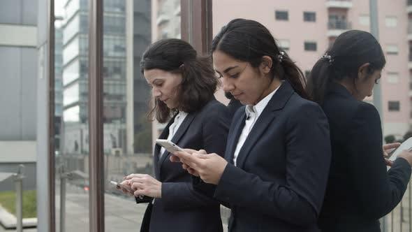 Thumbnail for Focused Businesswomen Using Smartphones