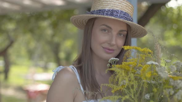 Thumbnail for Portrait Adorable Young Woman in Straw Hat and White Dress Looking at the Camera Smiling While