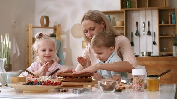 Thumbnail for Blonde Woman Making Layered Cake with her Kids