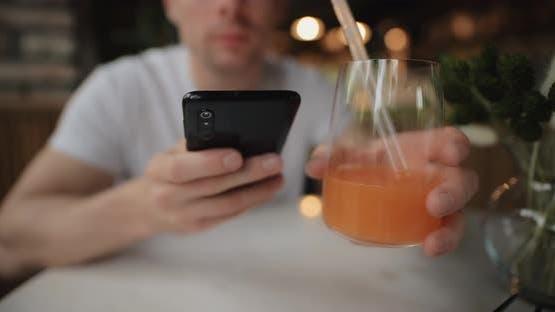 Closeup Man Drinks Fruity Juice in Restaurant Looking Into Smartphone