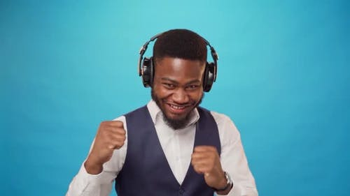 Joyful African Man Listening to Music with Headphones and Dancing to It Against Blue Background