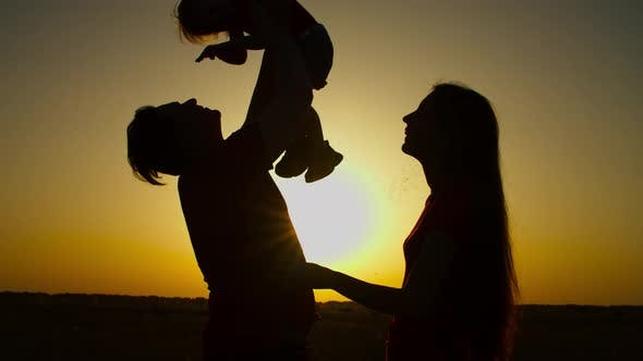 Thumbnail for Cheerful Family with Baby Girl Relaxing at Sunset