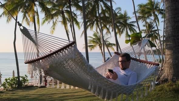 Man Enjoying Vacation on Sea Shore and Swinging in Hammock