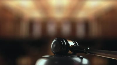Judge is Hitting Gavel Off a Block in Courtroom