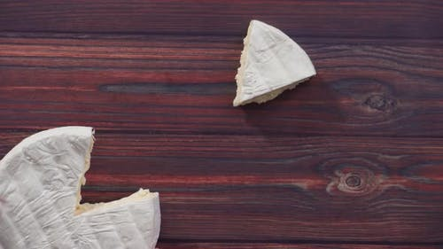 Flat lay. Sliced French triple cream brie cheese on a dark wooden background.