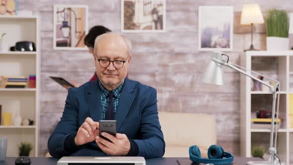 Elderly Man with Glasses Browsing on Mobile Phone