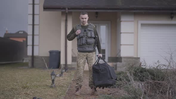 Thumbnail for The Young Soldier in Military Closes with Big Bag Standing in Front of the House