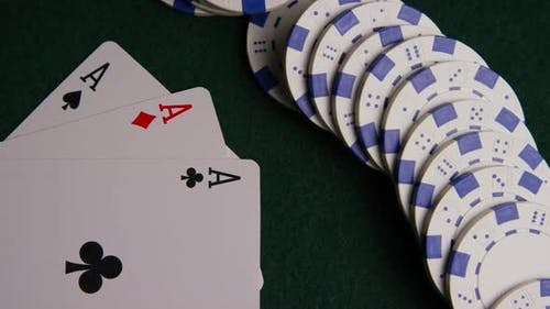 Rotating shot of poker cards and poker chips on a green felt surface - POKER 054