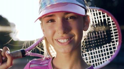 Hübsche junge Frau, die in die Kamera blickt und lächelt