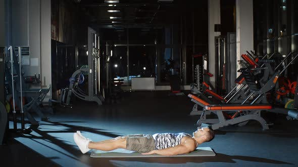 Thumbnail for Male Athlete Workout in Gym Doing Sit Up Exercises Lifting Straight Legs to Torso on Floor Mat
