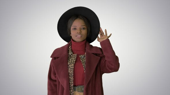 Thumbnail for Cute afro model in coat touching hat walking on gradient