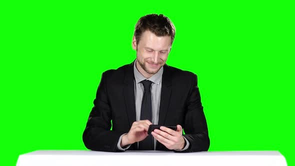 Thumbnail for Businessman Sitting at the Table and Uses Phone. Green Screen