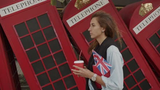 Thumbnail for Attractive Girl Walking on a Background of Red British Phones. Drinks Coffee and Sightseeing