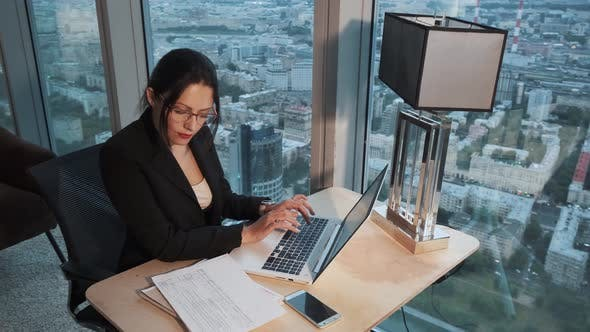 Thumbnail for Portrait of Business Woman with Glasses in the Office. Girl Sitting at the Table and Working on a