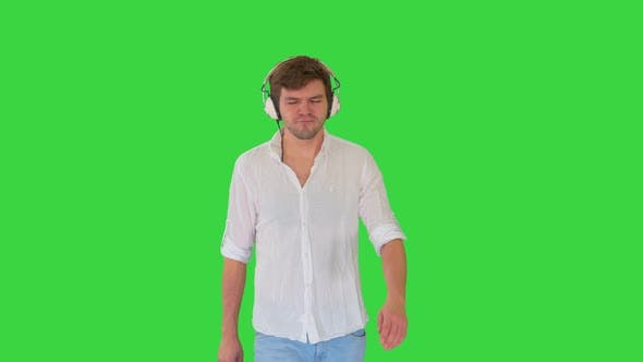 Thumbnail for Young Man in Headphones Listening To Music and Enjoying It Walking with Closed Eyes on a Green