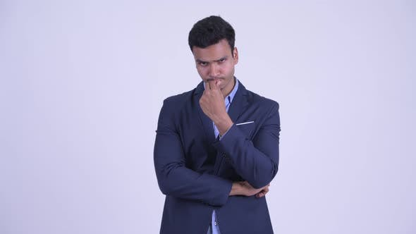 Serious Young Indian Businessman Thinking and Looking Down
