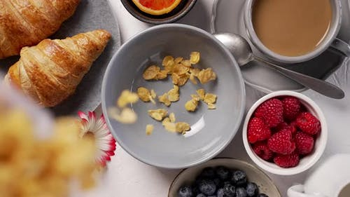 Pouring Cornflakes Into Breakfast Bowl