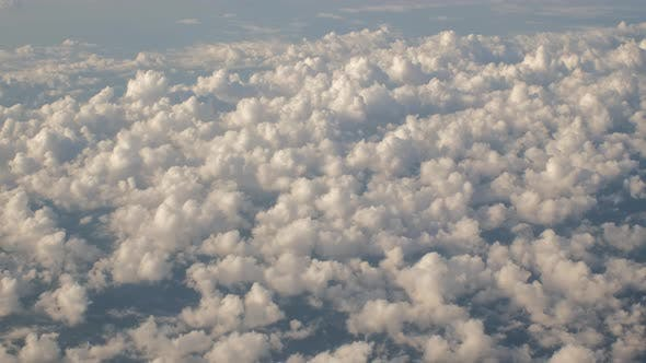 Fluffy Clouds From Above While Flying in Airplane